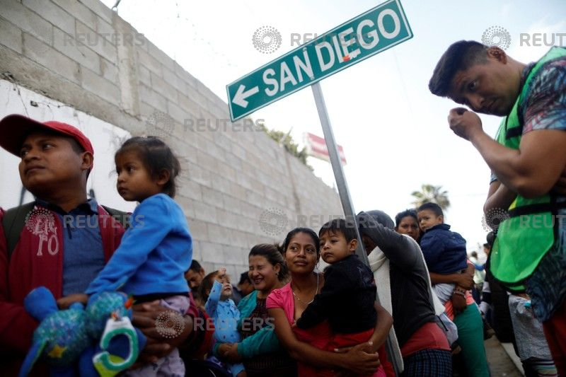 Caravan of Central American asylum seekers arrive at USA  border wall