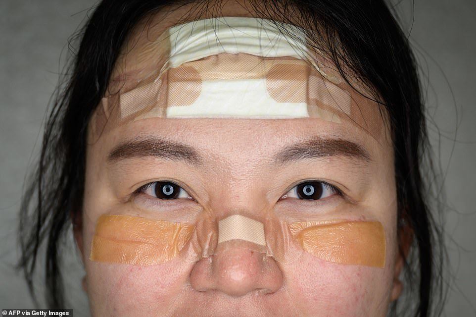 25921958-8108215-The_pads_plasters_and_tape_protect_nurse_Kim_Do_yeon_s_face_from-a-74_1584100574775.jpg
