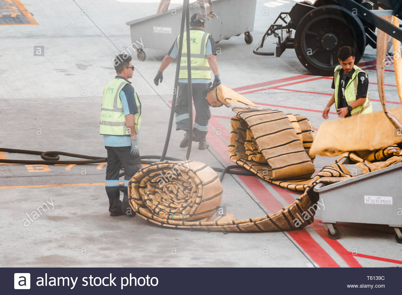asian-ground-crew-carrying-yellow-air-conditioning-ventilation-pipe-to-be-connected-into-a-parking-airplane-to-cool-down-the-cabin-T6139C.jpg